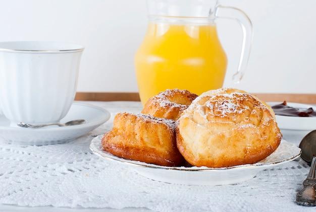Petit-déjeuner sain avec des petits gâteaux, du pain grillé, de la confiture et du jus