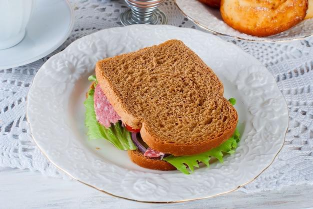 Petit-déjeuner sain avec des sandviches, du pain grillé, de la confiture et du jus