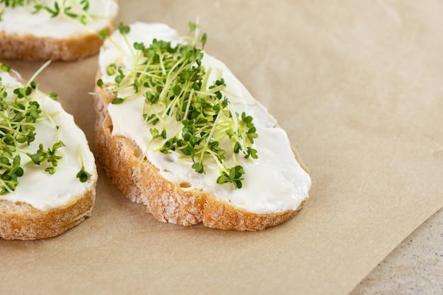 Petit-déjeuner sain. sandwich au fromage à la crème et micro-verts.