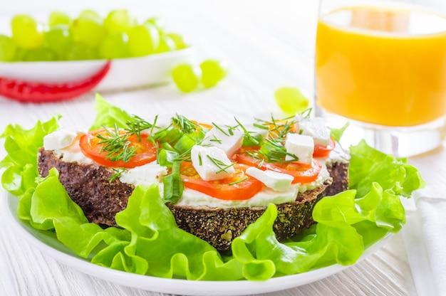 Petit-déjeuner sain: sandwichs avec légumes et herbes, jus d'orange et raisins