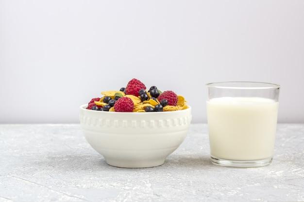 Petit-déjeuner sain et savoureux: bol avec des flocons de maïs et des baies et un verre de lait.