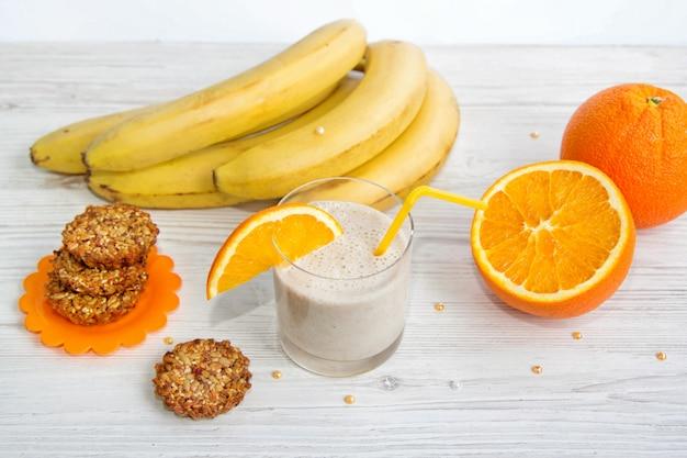 Petit-déjeuner sain. smoothie banane avec tranche d'orange, biscuits à base de graines de tournesol, de sésame et de miel