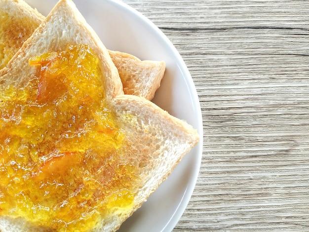 Petit-déjeuner sain avec des toasts pour le petit-déjeuner (avec de la confiture d'oranges et d'ananas) sur une table en bois.