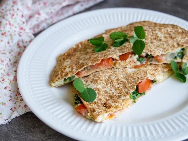 Petit-déjeuner sain végétarien composé de pain pita fin fondu, de fromage, de tomate et d'herbes