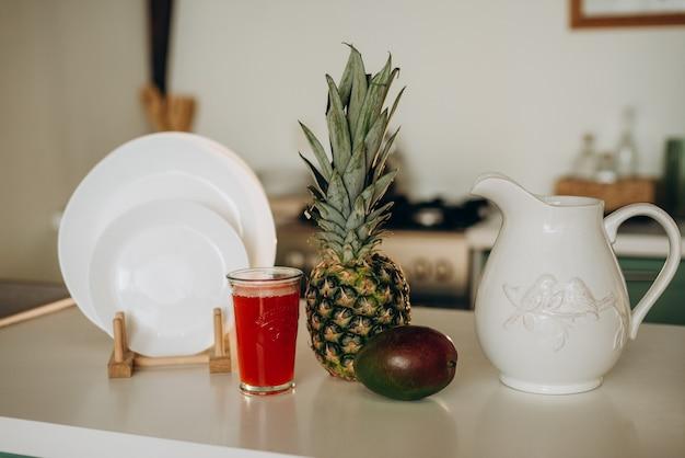 Petit-déjeuner sain, verre de pamplemousse frais, mangue, vaisselle blanche ananas
