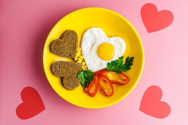 Petit déjeuner de la saint-valentin. oeuf au plat en forme de coeur et pain dans une assiette jaune sur fond rouge