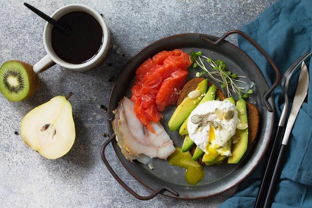 Petit-déjeuner de la saint-valentin sandwich aux œufs durs avec café d'avocat et saumon fumé vue de dessus