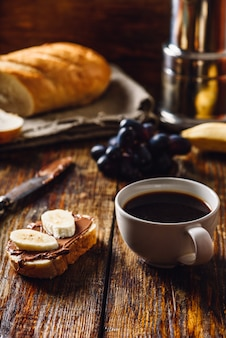 Petit-déjeuner avec sandwich aux fruits et café.