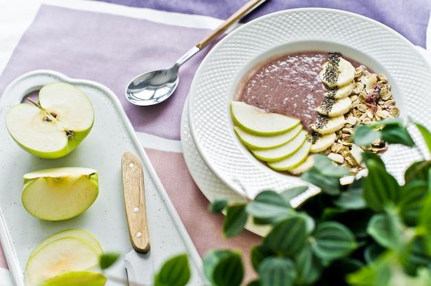 Petit-déjeuner santé, bol à smoothies avec banane, pomme, graines de chia, granola et yogourt.