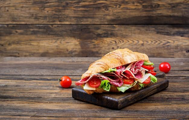 Petit déjeuner savoureux. croissant appétissant au salami et au fromage et aux tomates