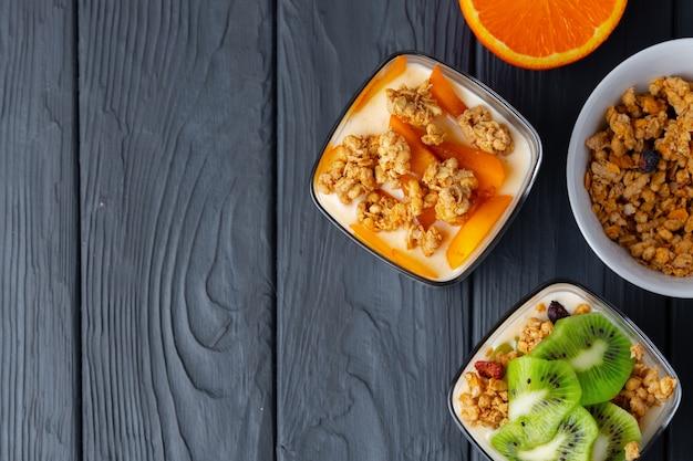 Petit déjeuner savoureux avec granola, yaourt et fruits dans un bol en verre