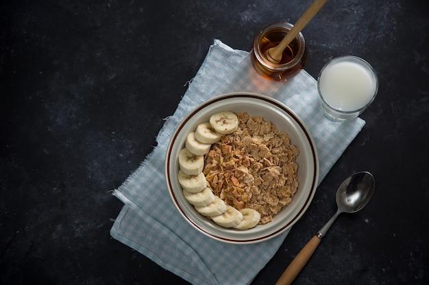 Petit déjeuner savoureux et sain : fruits, corn flakes, lait et miel.