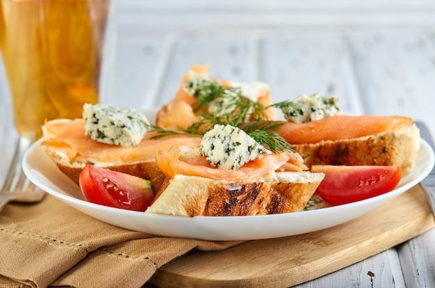 Petit déjeuner savoureux. sandwiches au saumon et au fromage et tomates cerises sur un blanc en bois