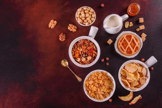 Petit déjeuner savoureux et utile avec des flocons, du lait, des noix et des fruits secs