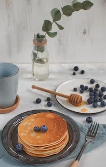 Petit déjeuner scène, avec des crêpes, des myrtilles et du miel sur la cuillère à miel, vase avec eucalyptus