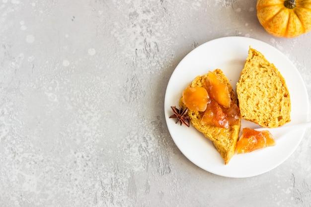 Petit-déjeuner avec des scones de citrouille épicés, une tasse de thé et du lait.