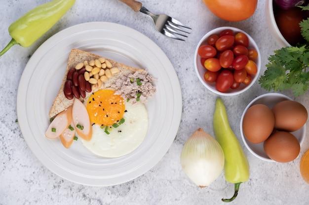 Le petit-déjeuner se compose d'œufs au plat, de saucisses, de porc haché, de pain, de haricots rouges et de soja sur une assiette blanche.