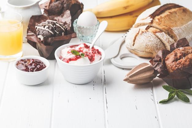 Petit déjeuner servi avec muffins, jus de fruits, pain frais et parfait sur une table en bois blanche.