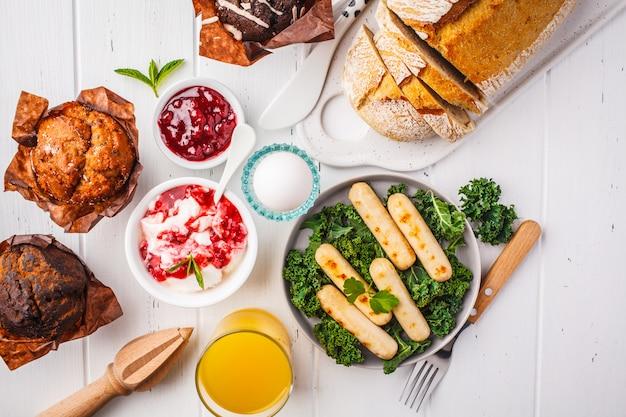 Petit déjeuner servi avec muffins, saucisses grillées, jus de fruits, pain frais et parfait sur une table en bois blanc.