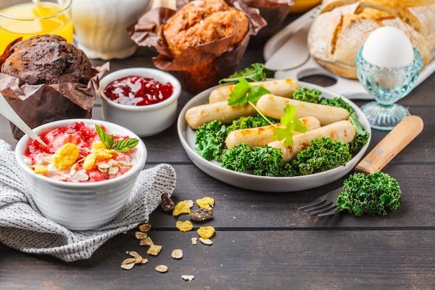 Petit déjeuner servi avec muffins, saucisses grillées, jus de fruits, pain frais et parfait sur une table en bois sombre.