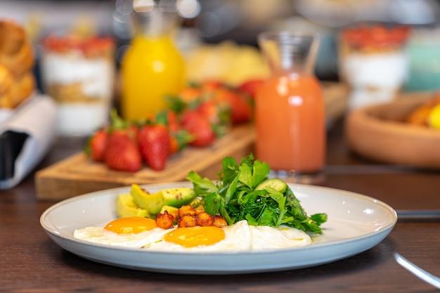 Petit-déjeuner servi avec des œufs au jus d'orange croissants fraises alimentation équilibrée