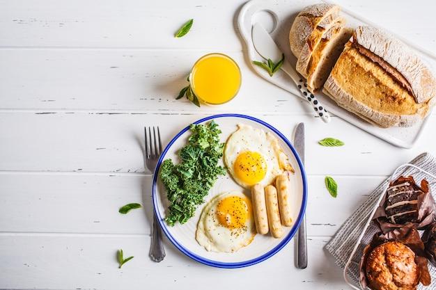 Petit déjeuner servi avec œufs au plat, salade, muffins et jus d'orange sur une table en bois blanche.
