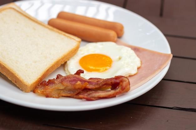 Petit déjeuner simple. pain grillé, œuf au plat, saucisse, jambon et bacon.