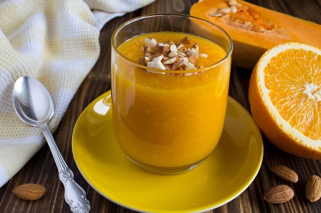 Petit déjeuner : smoothie au potiron, orange et amande sur le fond en bois