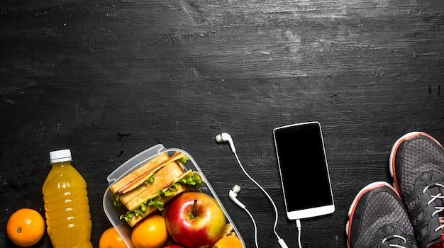 Petit-déjeuner sportif jus d'orange avec sandwichs et fruits