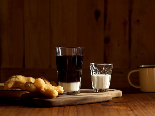 Petit-déjeuner de style thaïlandais avec café et bâtonnets de pâte frits sur table en bois