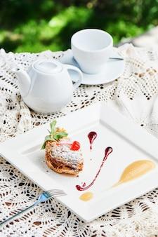 Un petit déjeuner sucré de crumble de dessert avec de la compote de pommes et une garniture aux cerises servi sur une assiette blanche et un service à thé