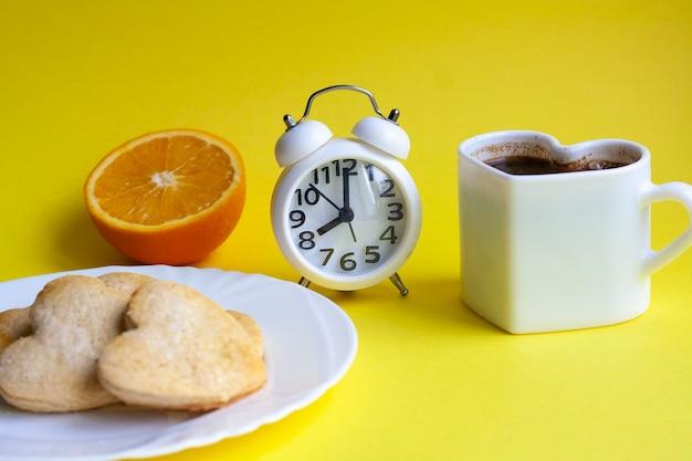 Petit-déjeuner sur une table jaune, une demi-orange, du café, des biscuits sur une assiette blanche et un réveil