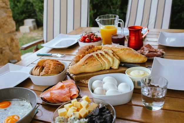 Petit déjeuner à table pain frais sur la table petit déjeuner en terrasse pour une famille nombreuse