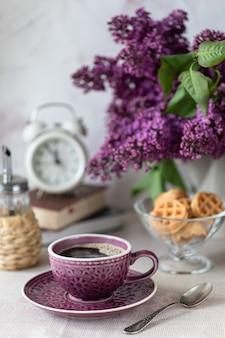 Petit déjeuner tasse de café, gaufres, lait et crème et fleurs lilas. matin