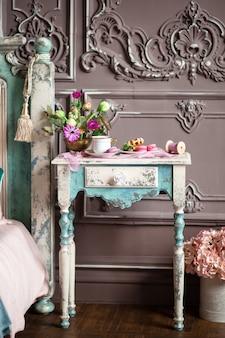 Petit déjeuner avec une tasse de thé, des gaufres au miel et des macarons sur la coiffeuse dans la chambre design