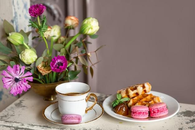 Petit-déjeuner avec une tasse de thé, des gaufres au miel et des macarons
