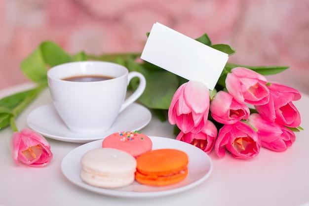 Petit-déjeuner avec tasse de thé, macarons et tulipes roses