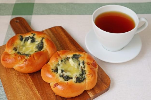 Petit-déjeuner avec thé chaud, brioches au fromage et épinards