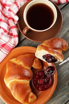 Petit déjeuner avec thé et grand croissant frais sur bois