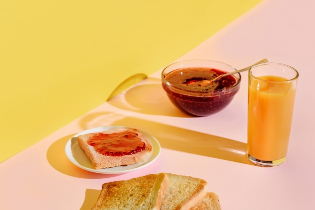 Petit déjeuner de toasts à la confiture et au jus d'orange sur un fond rose et jaune vif, chargé de soleil.