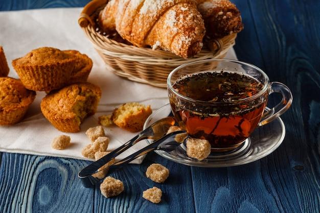 Petit déjeuner traditionnel avec thé noir et croissants, fond en bois vintage, selective focus