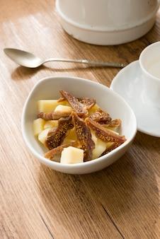 Petit-déjeuner de tranches de figue séchée avec pecorino à côté d'une tasse de café