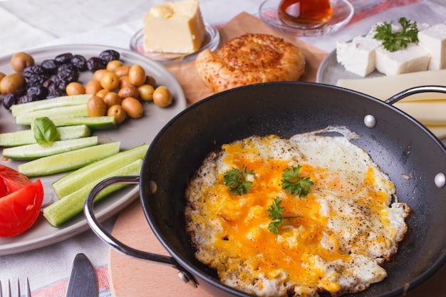Petit déjeuner turc traditionnel - œufs au plat, légumes frais, olives, fromage, gâteaux et thé