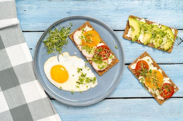 Petit déjeuner varié, apéritifs sandwichs avec pain, fromage à la crème, radis, vue de dessus.