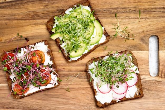 Petit-déjeuner varié snacks sandwichs avec pain complet grille-pain avec fromage à la crème radis avocat