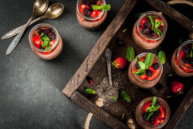 Petit déjeuner végétalien sain. dessert. nourriture alternative. pudding aux graines de chia, fraises fraîches, mûres et menthe. , dans un vieux plateau en bois. vue de dessus