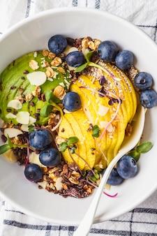 Petit déjeuner végétalien sain. granola à l'avocat, superaliments, baies et fruits dans un bol blanc, vue de dessus.