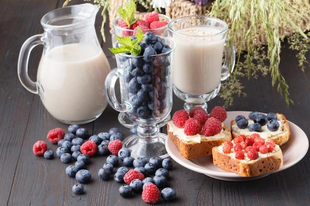 Petit déjeuner végétalien sain. granola à l'avoine avec du lait d'avoine et des baies sur une table en bois.