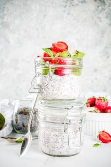 Petit-déjeuner végétalien sain, yaourt avec graines de chia et fruits frais, fraises, kiwi.espace de copie de fond en marbre blanc