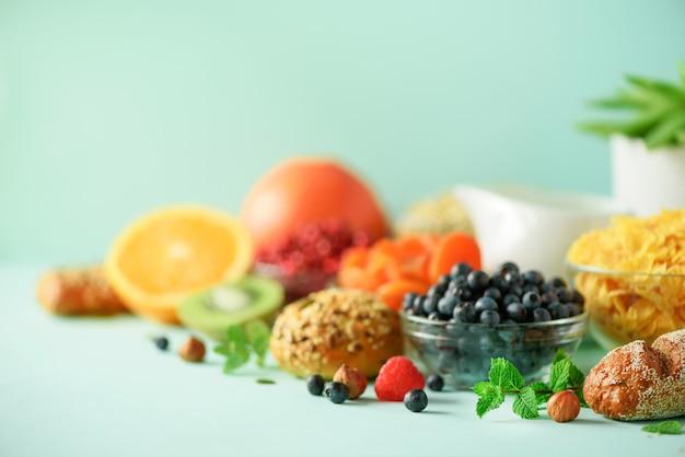 Petit déjeuner végétarien. œuf à la coque, flocons d'avoine, noix, fruits, baies, lait, yaourt, orange, banane, pêche sur fond jaune. régime alimentaire sain.